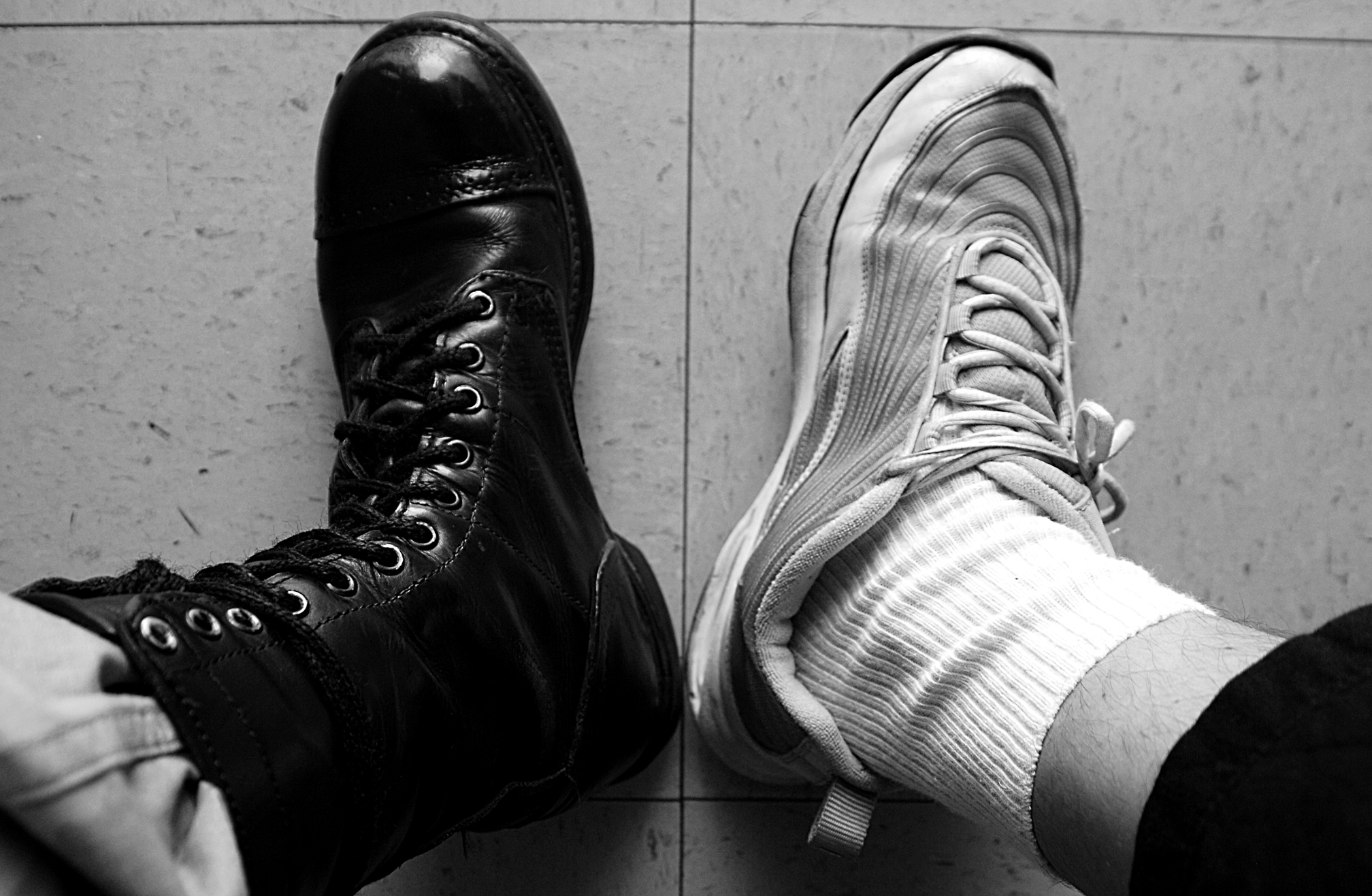 left foot in army boot and right foot in sport shoe